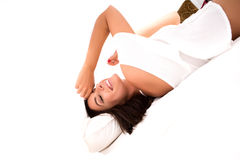 A beautiful young woman under the sheets in the bed Stock Images