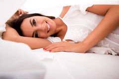 A beautiful young woman under the sheets in the bed Royalty Free Stock Images