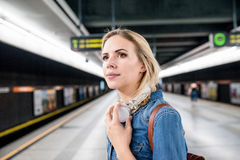 Beautiful young woman at the underground platform, waiting. Beautiful young woman in denim shirt with earphones, standing at the underground platform, waiting Stock Photo