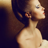Beautiful young woman undressed holding furs. Portrait of a beautiful young woman undressed holding luxurious fur coat after ball. Arty make-up of golden foil Stock Image