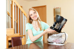 Beautiful young woman unpacking new coffeemaker at home interior Stock Photos