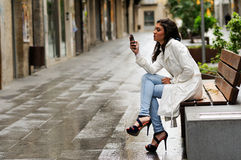 Beautiful young woman in urban background talking on phone Royalty Free Stock Images