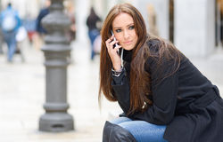 Beautiful young woman in urban background talking on phone Stock Images