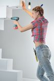 Beautiful young woman uses an electric drill Royalty Free Stock Photos
