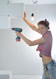 Beautiful young woman uses an electric drill Stock Image