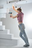 Beautiful young woman uses an electric drill Stock Photos