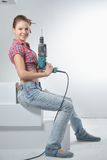 Beautiful young woman uses an electric drill Stock Images