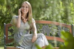 Beautiful young woman using cell phone on bench in park Stock Photos