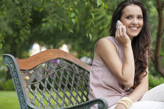 Beautiful young woman using cell phone on bench in park Stock Photo