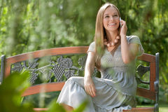 Beautiful young woman using cell phone on bench in park Royalty Free Stock Photo