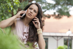 Beautiful young woman using cell phone in park Royalty Free Stock Images
