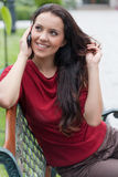 Beautiful young woman using cell phone on park bench Royalty Free Stock Photo