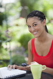 Beautiful Young Woman Using a Cellphone and Laptop Royalty Free Stock Photo