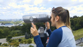 Beautiful young woman using coin paid binocular and looking at city stock footage