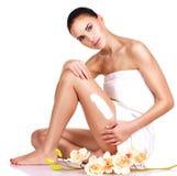 Beautiful young woman using cream. Stock Photography