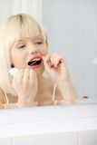 Beautiful young woman using dental floss Royalty Free Stock Photography