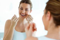 Beautiful young woman using dental floss in a home bathroom. Stock Photo