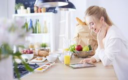 Beautiful young woman using a digital tablet in the kitchen stock photography