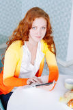 Beautiful young woman using a digital tablet in the kitchen Royalty Free Stock Images