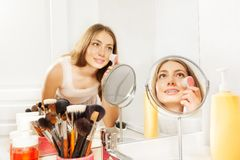Beautiful young woman using facial cleansing brush. Portrait of beautiful young woman seen in bathroom mirror, massaging her cheeks using facial cleansing brush stock photos
