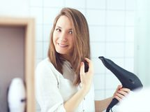 Beautiful young woman  using hair dryer drying hair. Hair care royalty free stock photo