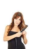 Beautiful young woman using hair straightener stock photography