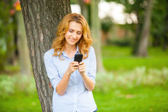 Beautiful young woman using her cellphone Stock Photos