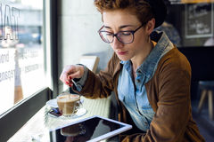 Beautiful young woman using her digital tablet in cafe. Stock Image