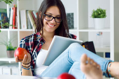 Beautiful young woman using her digital tablet at home. Royalty Free Stock Photo