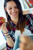 Beautiful young woman using her digital tablet at home. Royalty Free Stock Images