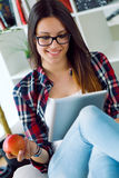 Beautiful young woman using her digital tablet at home. Royalty Free Stock Photos