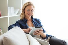 Beautiful young woman using her digital tablet at home. Stock Image