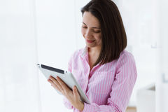 Beautiful young woman using her digital tablet in the office. Royalty Free Stock Photo