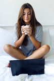 Beautiful young woman using her laptop amb drinking coffee at ho Royalty Free Stock Images