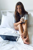 Beautiful young woman using her laptop amb drinking coffee at ho Stock Photo