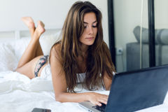 Beautiful young woman using her laptop in the bed. Stock Images