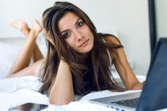 Beautiful young woman using her laptop in the bed. Royalty Free Stock Images