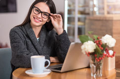 Beautiful young woman using her laptop in a coffee shop Stock Photos