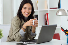 Beautiful young woman using her laptop at home. Stock Photo