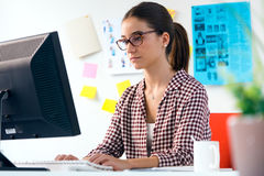 Beautiful young woman using her laptop in the office. Stock Images