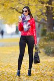 Beautiful young woman using her mobile phone in autumn. Royalty Free Stock Photo