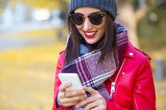 Beautiful young woman using her mobile phone in autumn. Stock Images