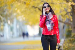 Beautiful young woman using her mobile phone in autumn. Stock Photos
