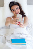 Beautiful young woman using her mobile phone in the bed. Royalty Free Stock Photos