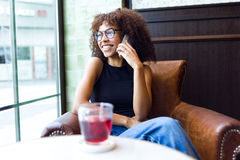 Beautiful young woman using her mobile phone in cafe. Royalty Free Stock Photo