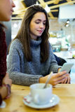 Beautiful young woman using her mobile phone at cafe shop. Royalty Free Stock Photo