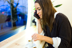 Beautiful young woman using her mobile phone at cafe shop. Royalty Free Stock Images
