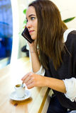 Beautiful young woman using her mobile phone at cafe shop. Stock Photos