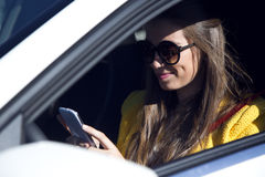 Beautiful young woman using her mobile phone in the car. Stock Photography