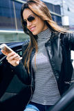 Beautiful young woman using her mobile phone in the car. Stock Images